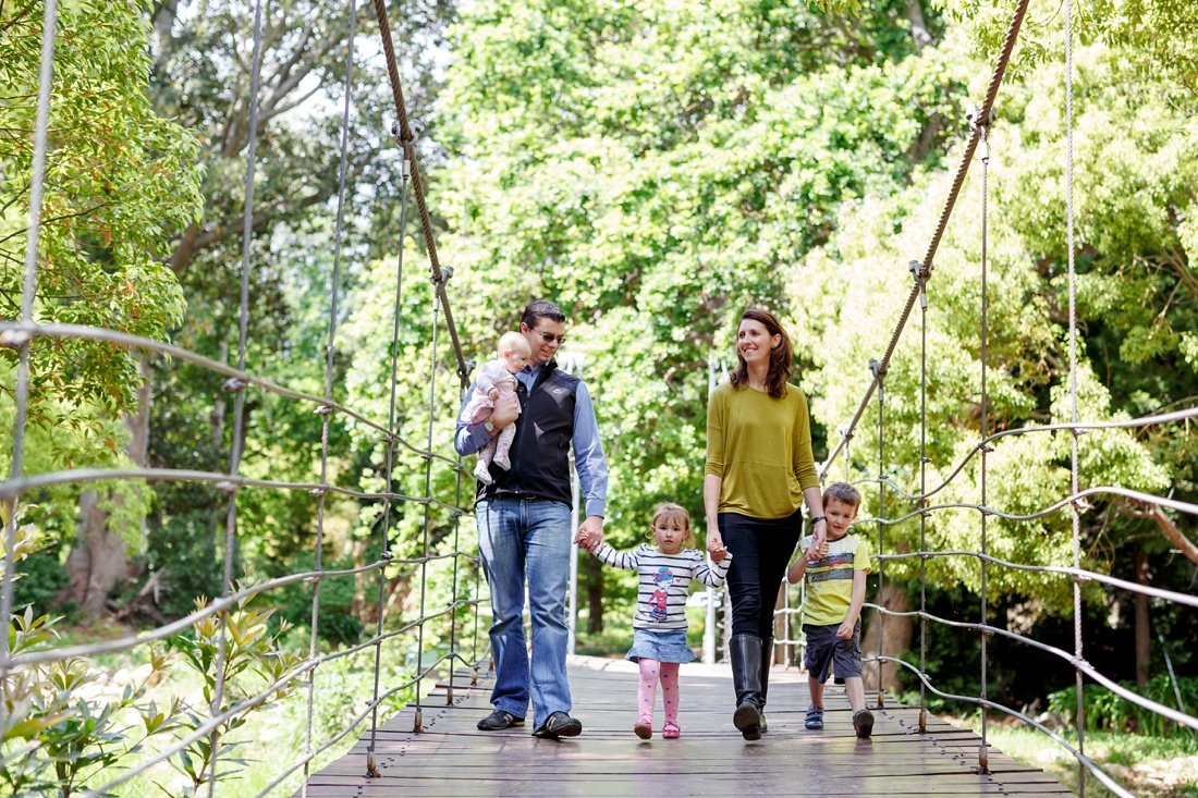 an image taken by Vividblue of a family, mom dad and three kids walking on a bridge holding hands