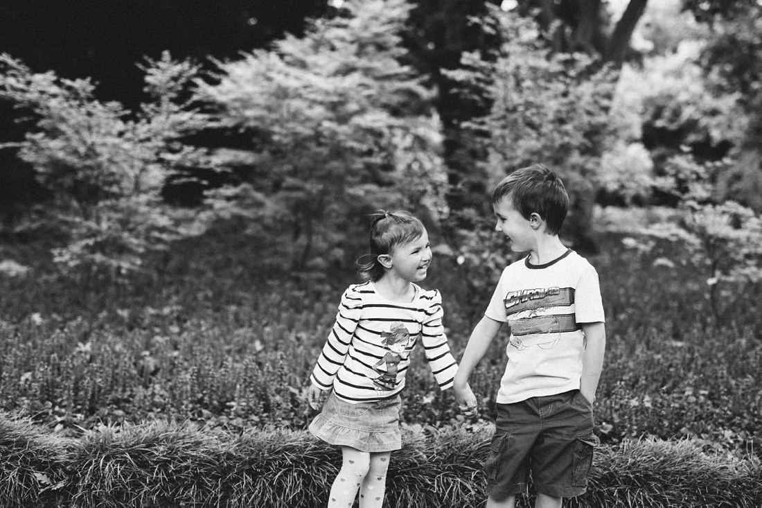 a black and white Image taken by VividBlue of a brother and sister holding hands.