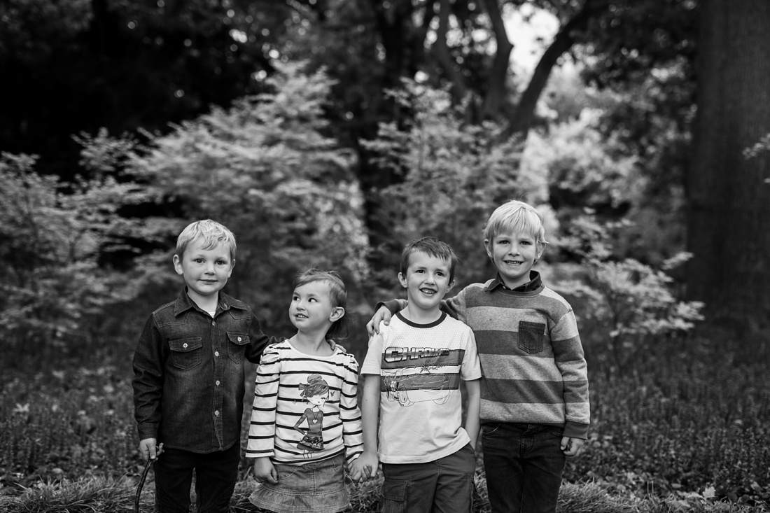a black and white image taken by Vividblue of four Kids standing with their arms around each other smiling
