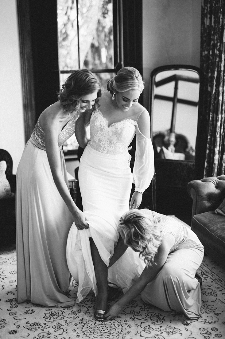 a black and white image taken by Vividblue of bridesmaids helping the bride put on her shoes at Molenvliet.