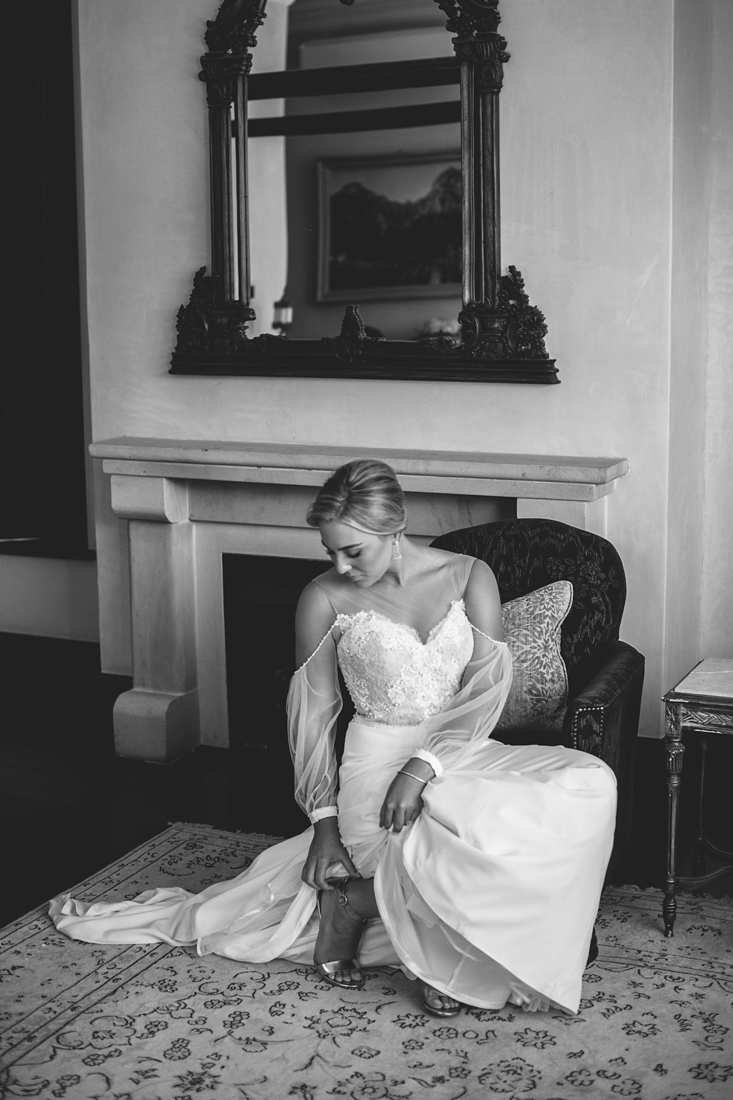 a black and white image taken by Vividblue of the bride putting on her shoes at Molenvliet.