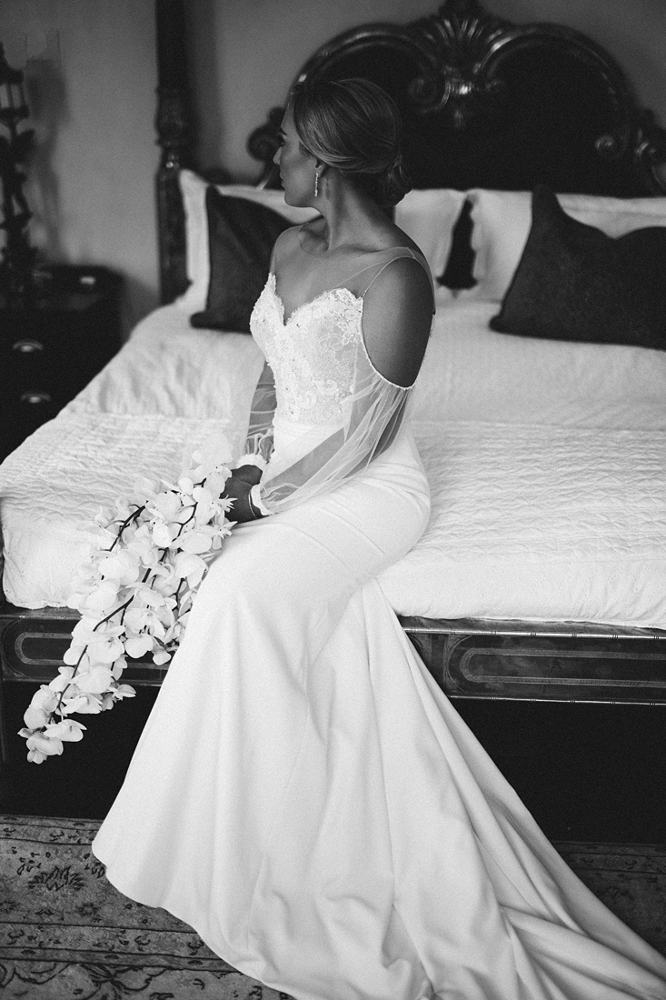 a black and white image taken by Vividblue of the bride in a tight fitted wedding dress with open sleeves holding her bouquet at Molenvliet.