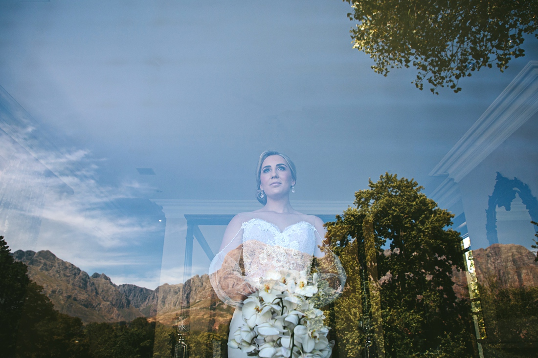 an image taken trow a window by Vividblue of the bride in a tight fitted wedding dress with open sleeves holding her bouquet at Molenvliet.