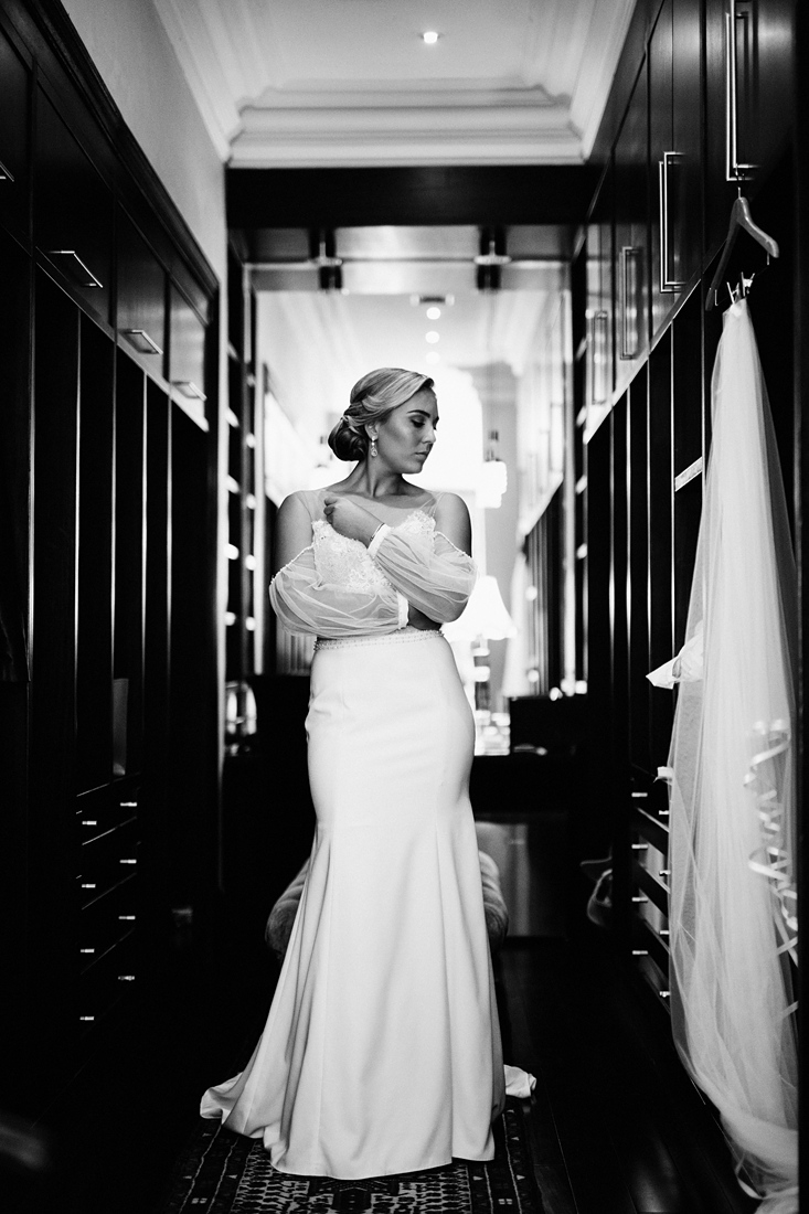 a black and white image taken by Vividblue of the bride in het tight fitted dress with open sleeves looking at her veil.