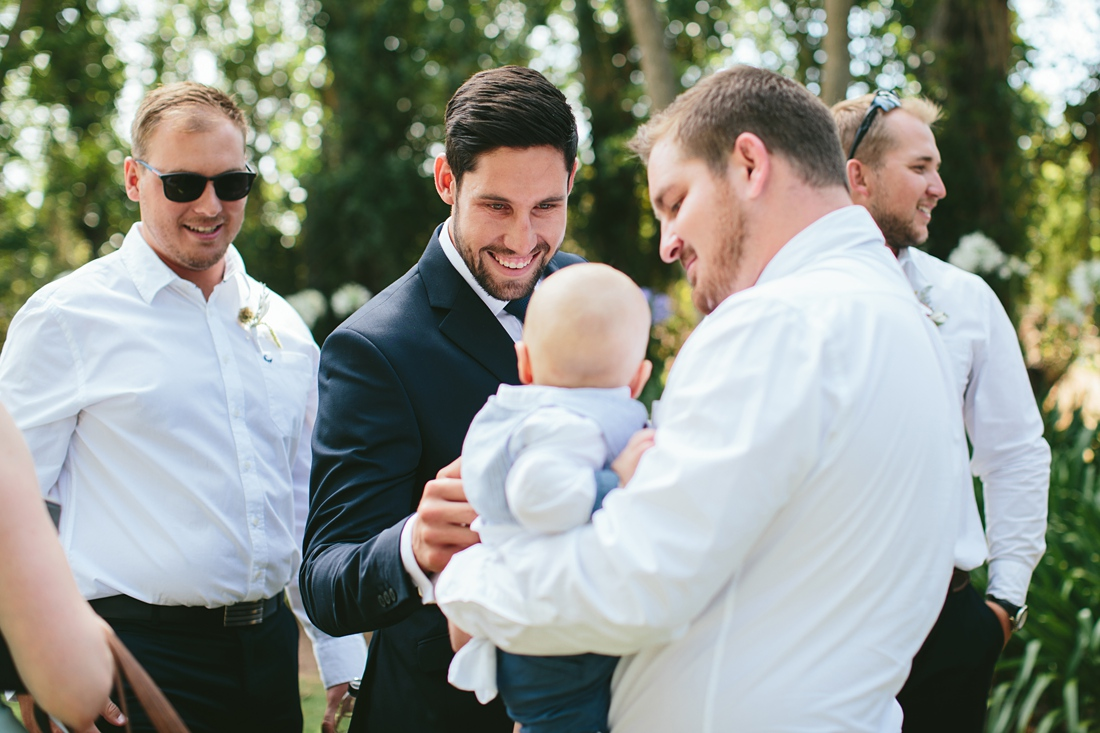 an image taken by Vividblue of one of the groomsmen holding a baby and smiling at Molenvliet