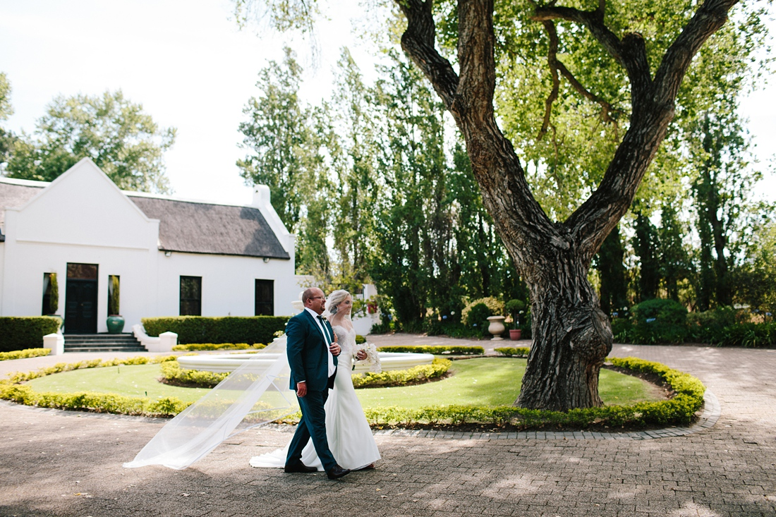 an Image taken by Vividblue of the bride and her dad walking at Molenvliet.