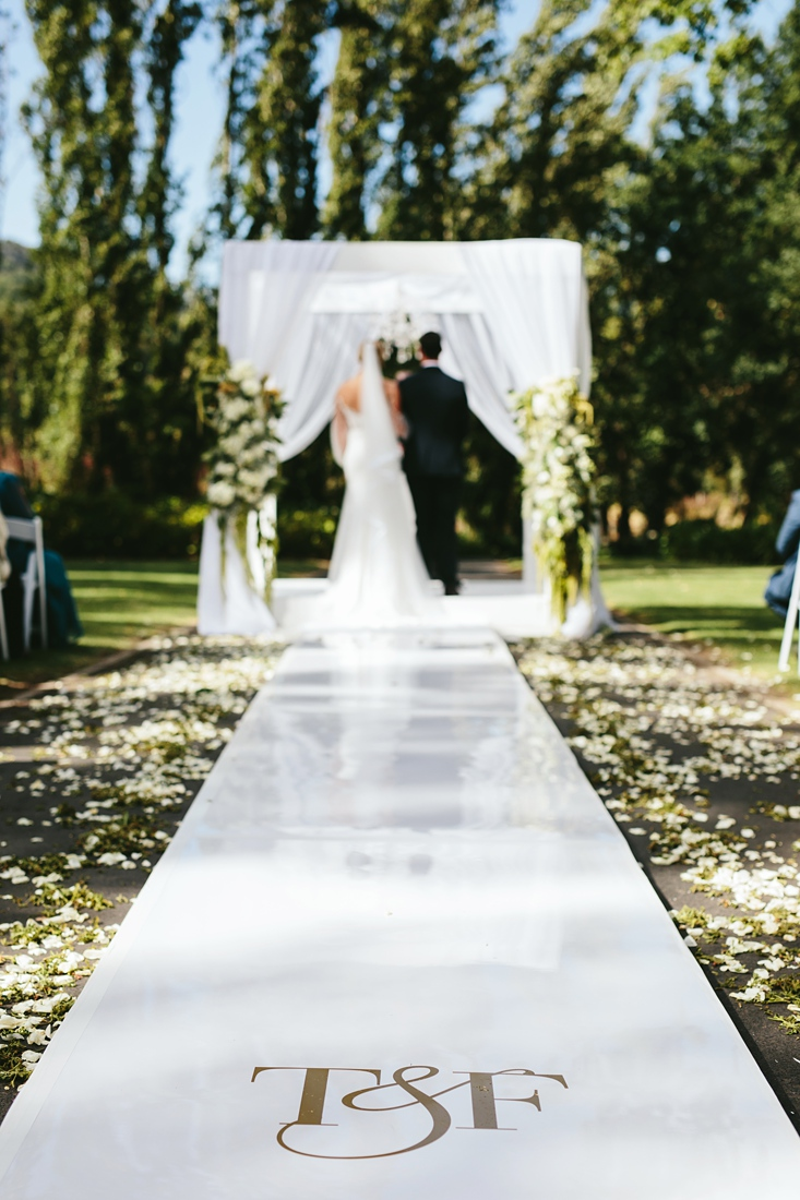 an image taken by Vividblue of the wedding isle and the arch with the bride and groom standing under it with rose petals on the side.