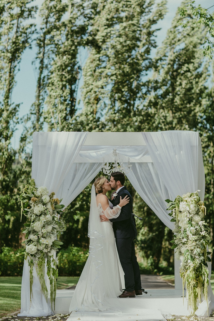 an image taken by Vividblue of the bride and groom kissing under an arch at Molenvliet.
