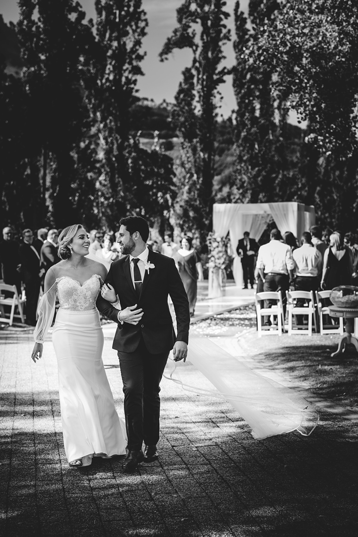 a black and white image taken by Vividblue of the bride and groom leaving the ceremony area happy at Molenvliet.
