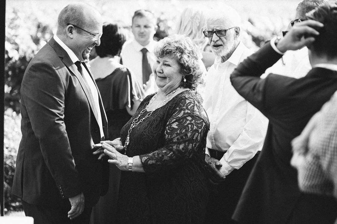 a black and white image taken by Vividblue of guests greeting each other at a Molenvliet wedding.