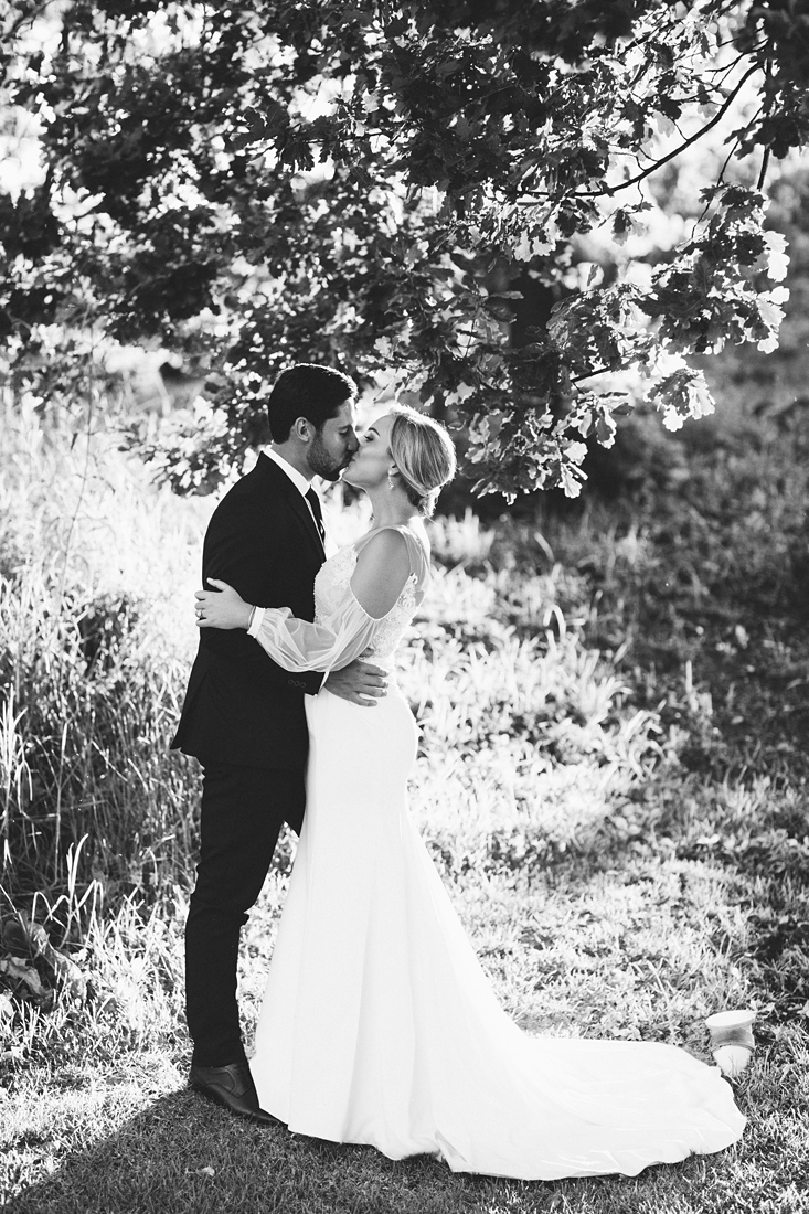 a black and white image taken by Vividblue of the bride and the groom kissing outside on Molenvliet.