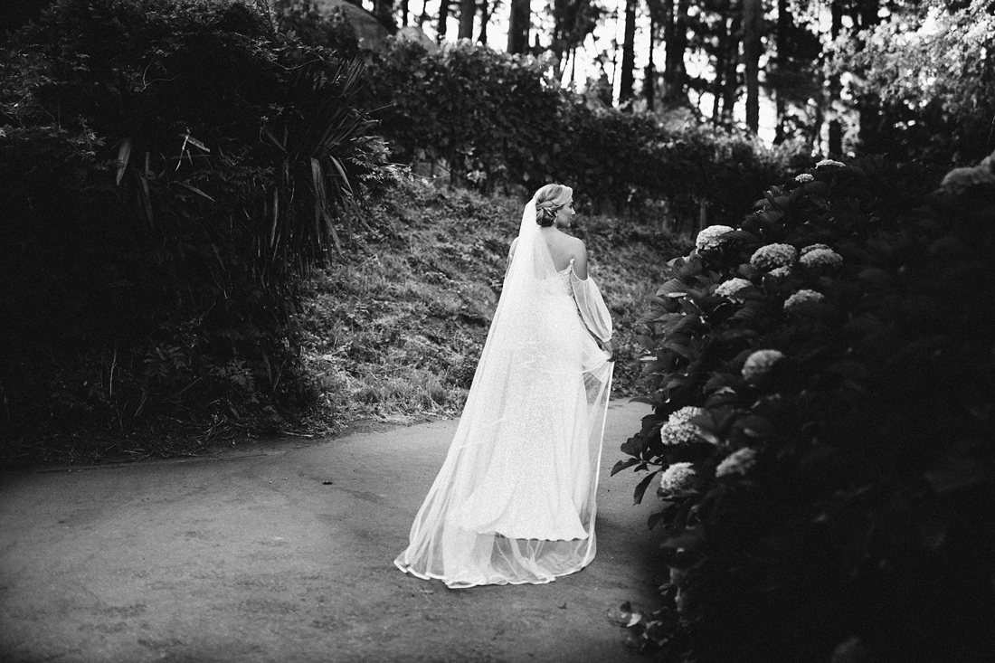 a black and white image taken by Vividblue of the bride walking away with her veil dragging behind her.