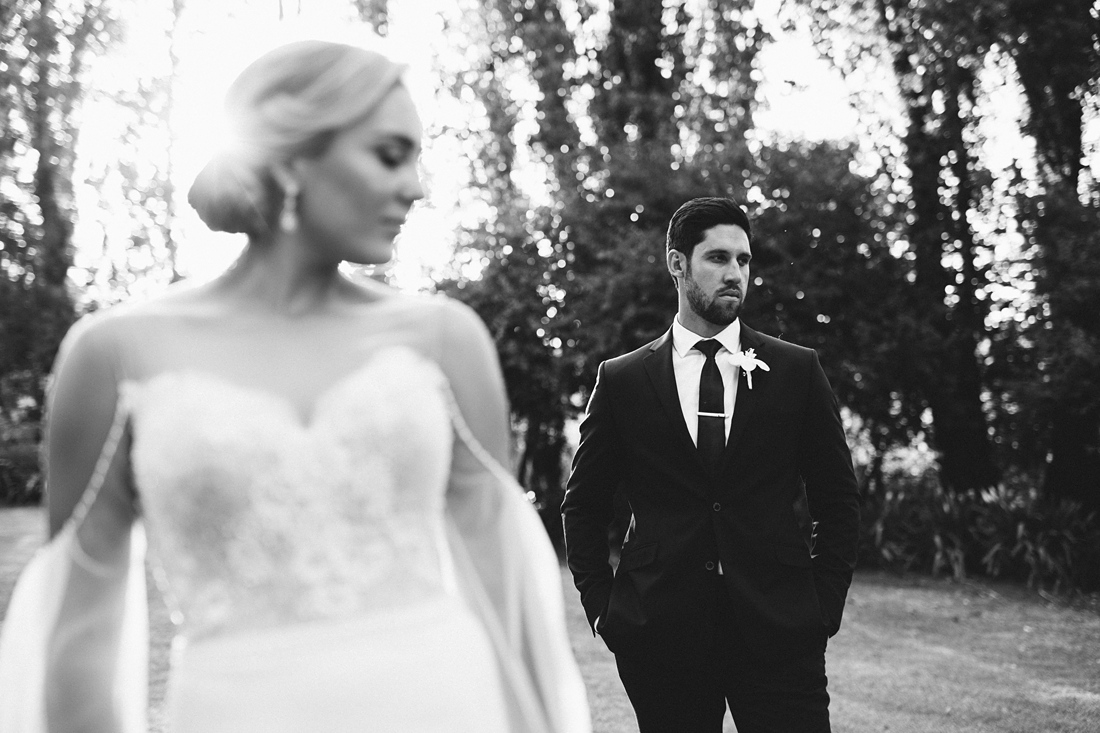 a black and white image taken by Vividblue of the bride and groom standing in the sunlight.