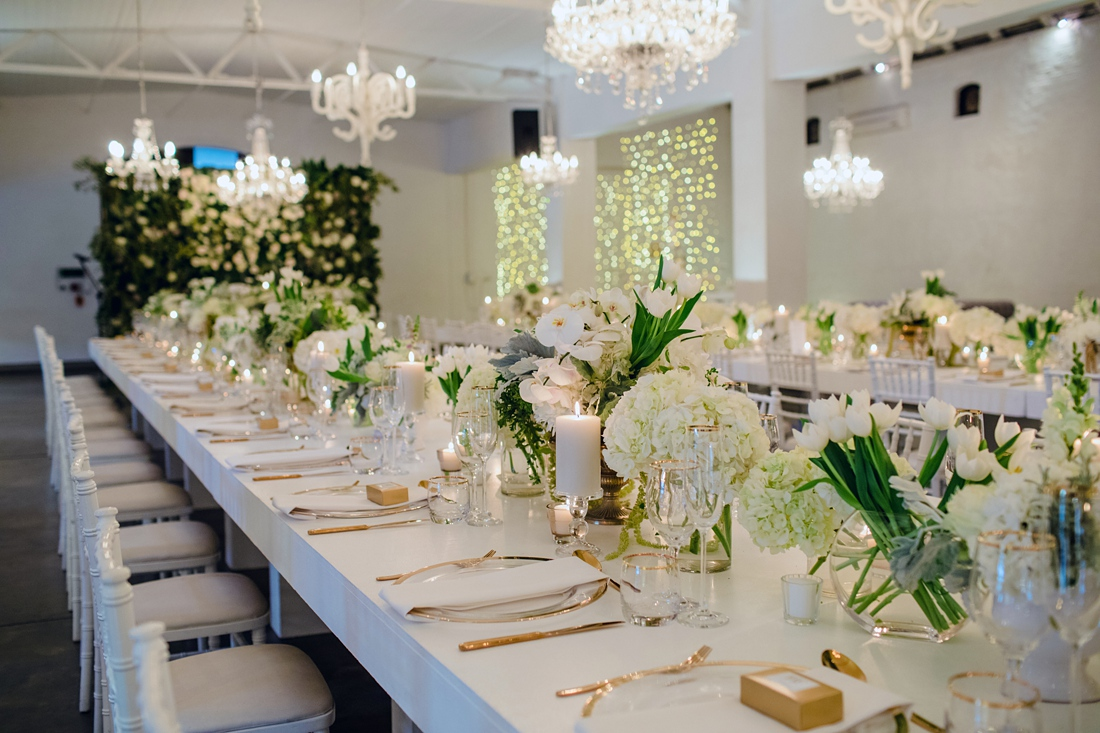 an Image taken by Vividblue of the decor, white tables and chairs with white floral with golden cutlery and a golden rim under plate