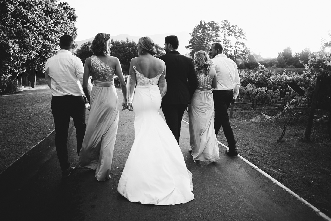 a black and white image taken by Vividblue of the wedding party walking and holding hands