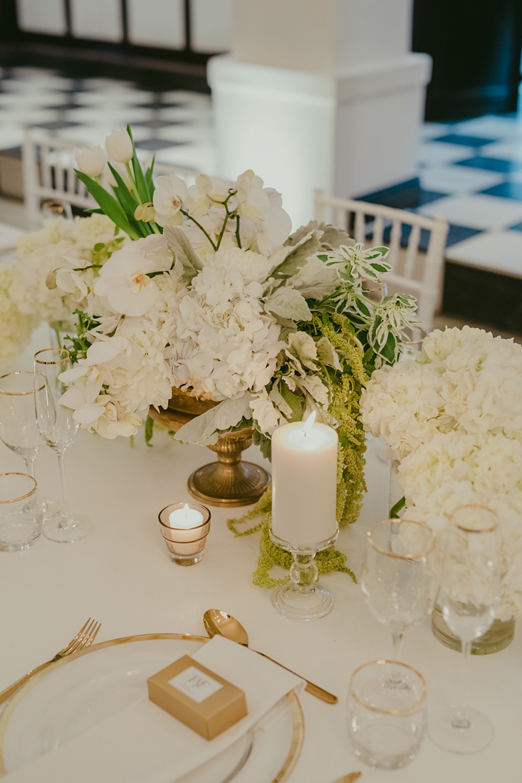 an Image taken by Vividblue of the table decor, white floral with golden cutlery and a golden rim under plate