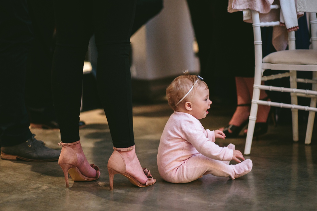an image taken by Vividblue of a baby siting on the ground while everyone is dancing.