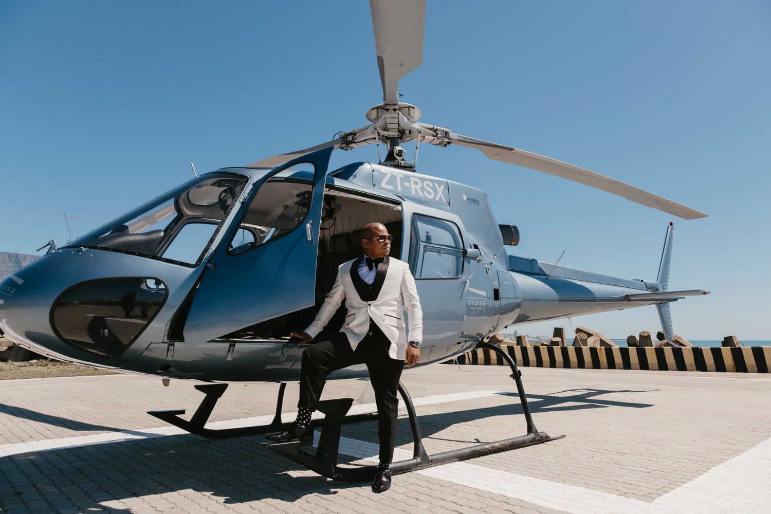 an image taken by Vividblue of the groom landing in a helicopter and making his entrance to the wedding at Val de Vie.