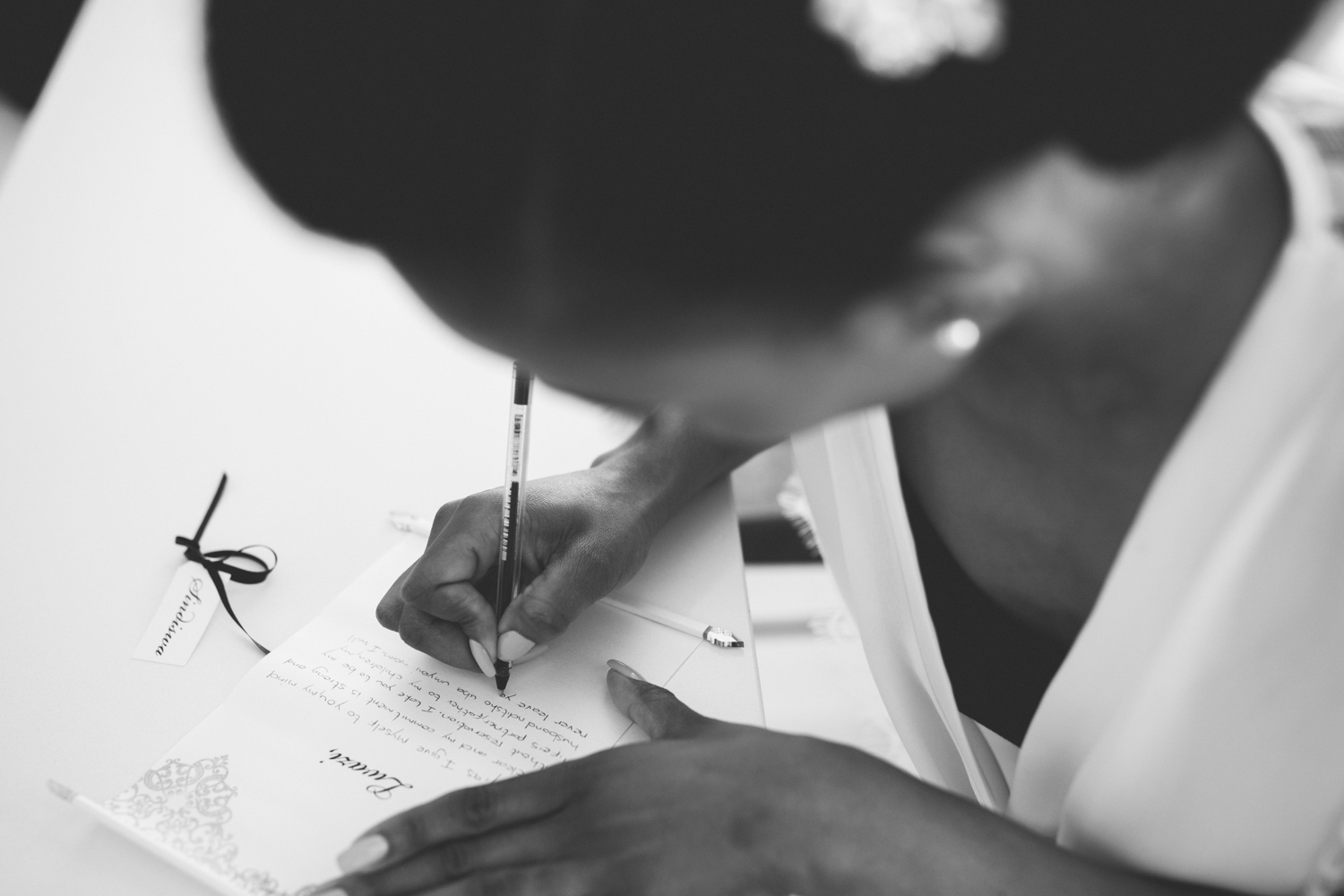 an black and white image taken by Vivideblue of the bride righting a letter.
