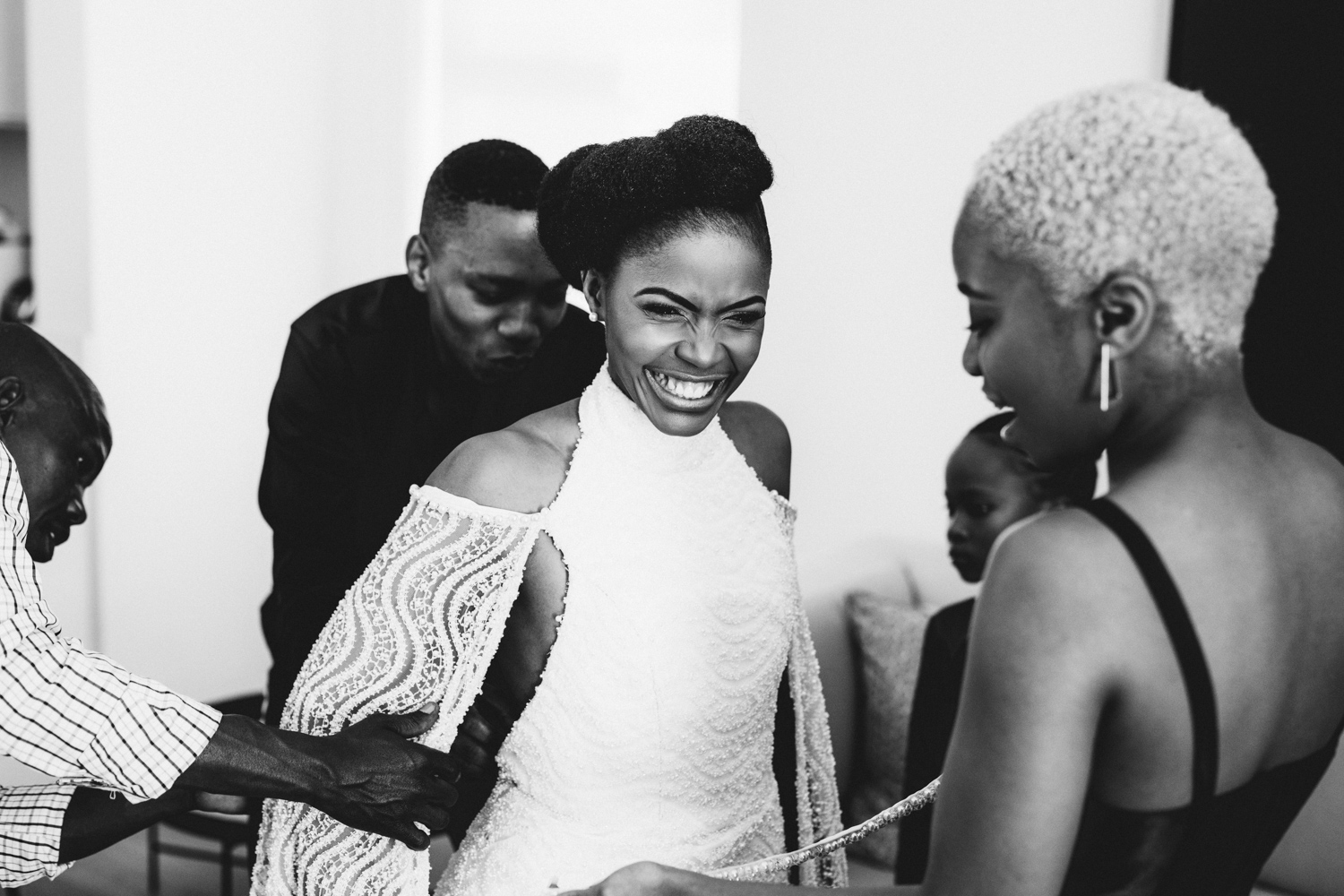 a black and white image taken by Vivideblue of the smiling bride and people helping her with the final details to her wedding dress at Val de Vie