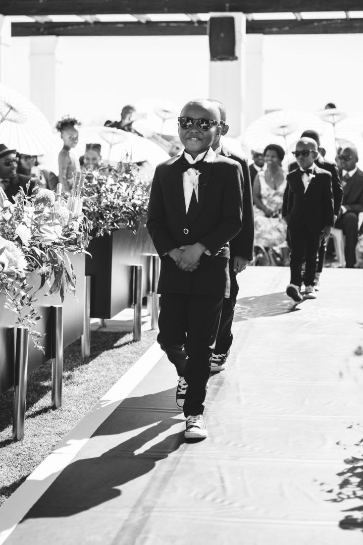 a black and white image taken by Vividblue of the young groomsmen walking down the isle at a wedding in Val de Vie.