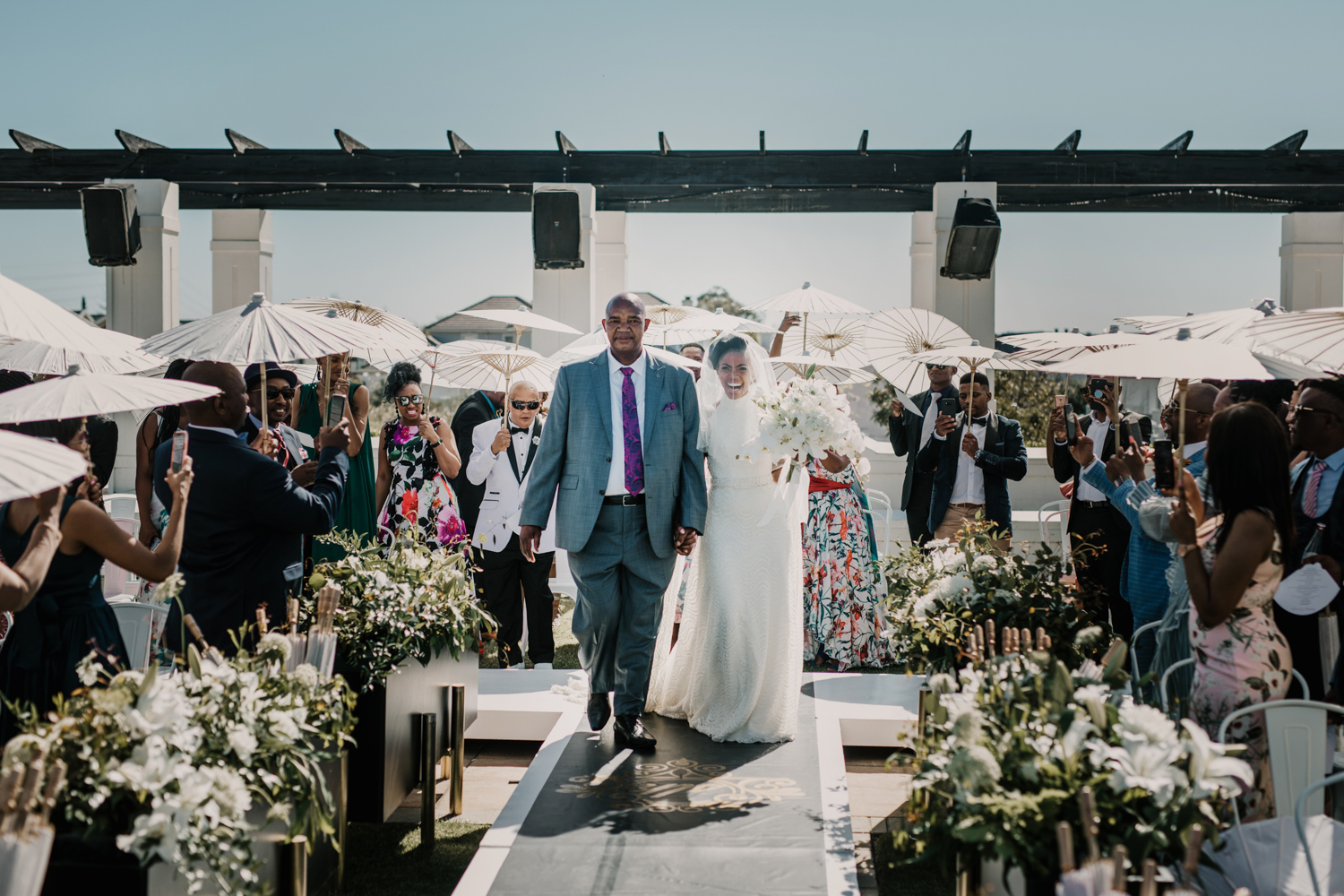 an Image taken by Vivideblue of the bride walking down the isle holding her bouquet on her wedding day at Val De Vie.