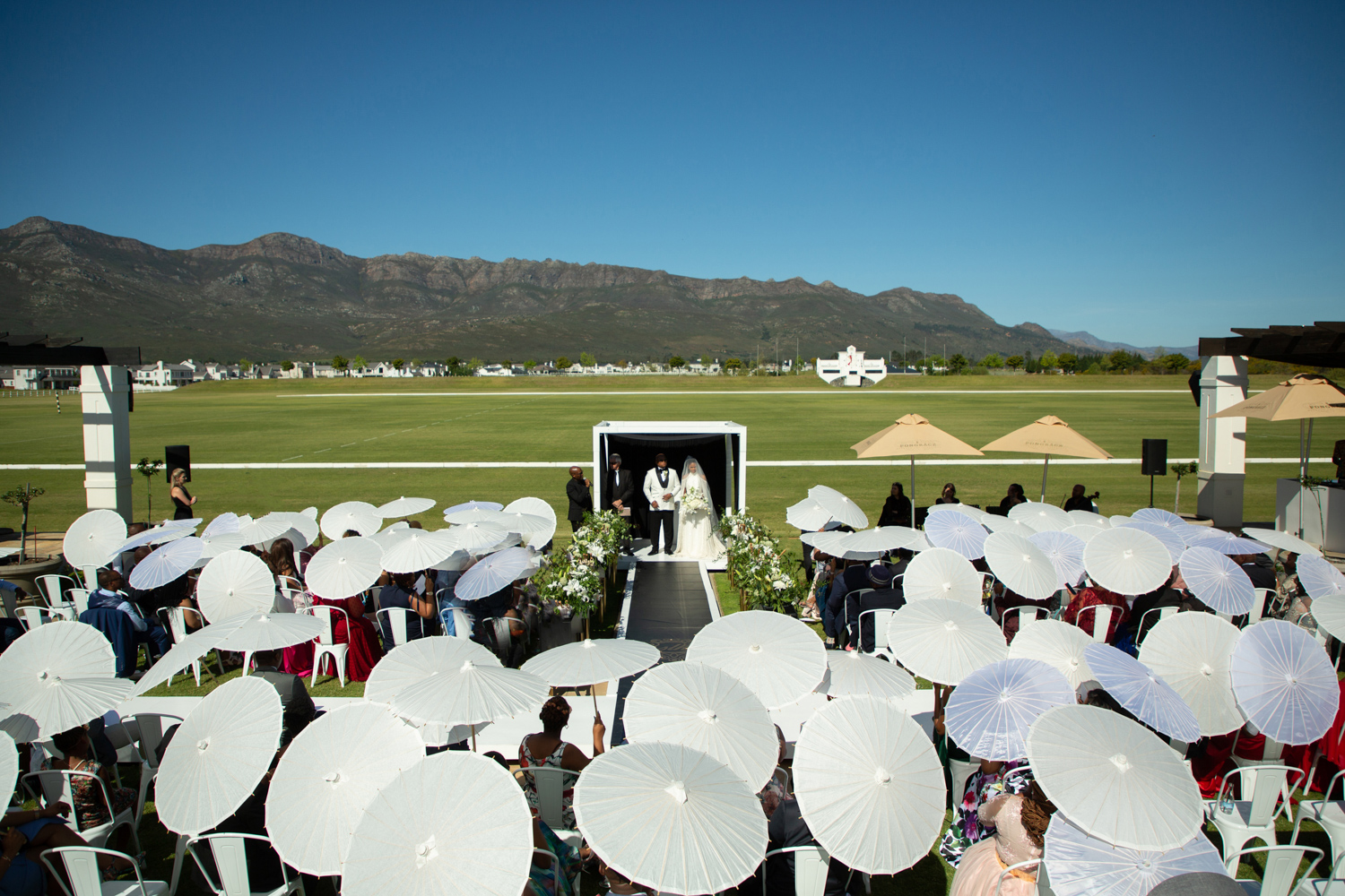 an image taken by Vividblue of the wedding ceremony with guests holding small white umbrellas at Val de Vie.