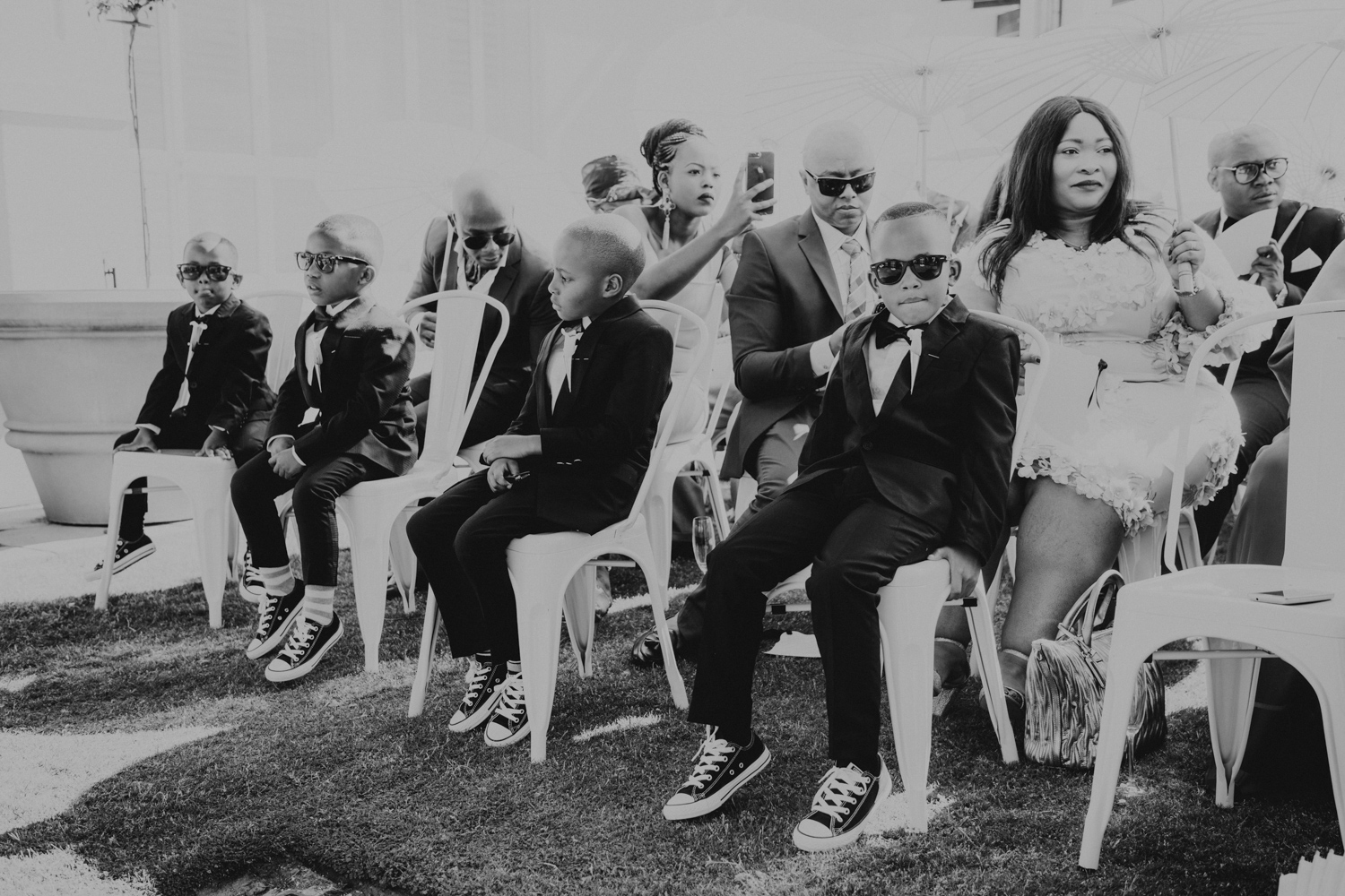 a black and white image taken by Vividblue of the boys in black suits siting in in the front row of the wedding ceremony at Val de Vie.