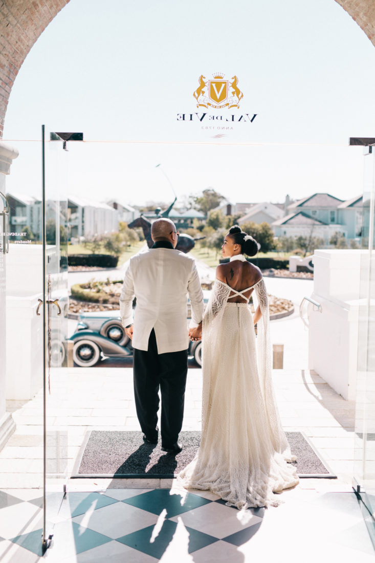 an image taken by Vivideblue of the wedding couple exiting the entrants of Val De Vie holding hands.