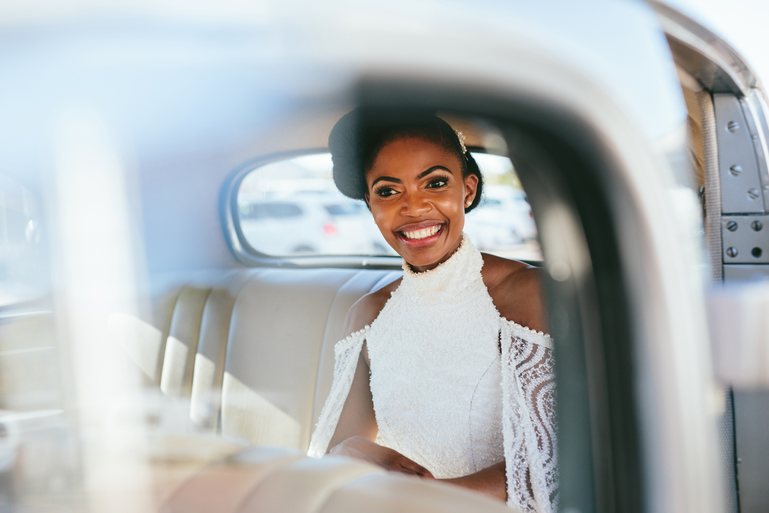 an image taken by Vividblue of the bride siting in the car and smiling by Val de Vie.