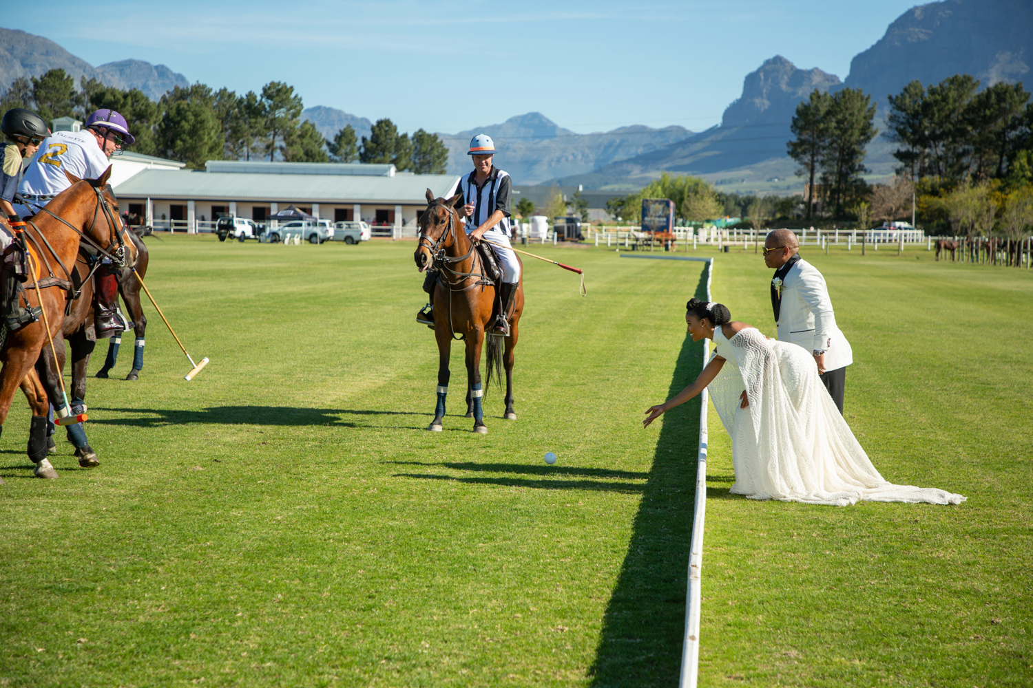 an image taken by Vividblue of the wedding couple next to a polo match where the bride trows the ball in.