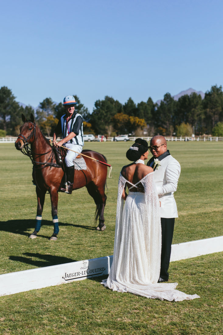 an Image taken by Vividblue of the groom and bride standing an holding hands next to a polo match at Val de Vie