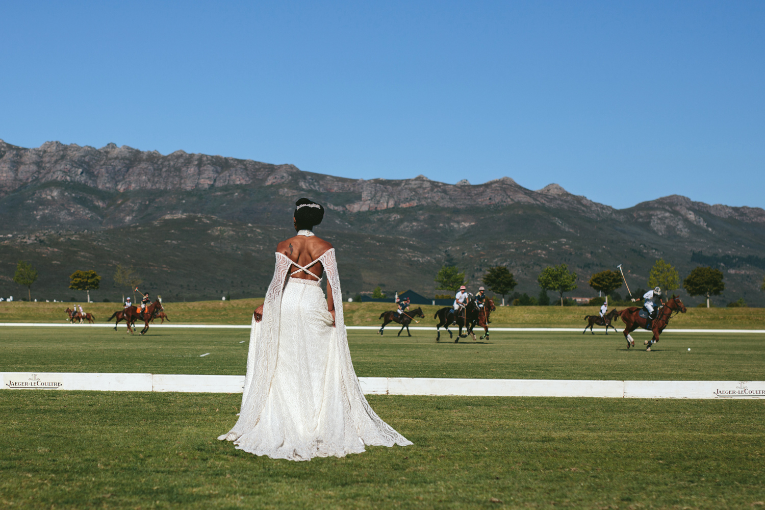 an Image taken by Vividblue of the bride standing next to a polo match at Val de Vie