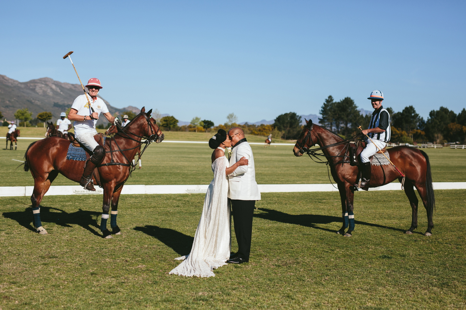 an Image taken by Vividblue of the groom and bride standing next to a polo match at Val de Vie and kissing.
