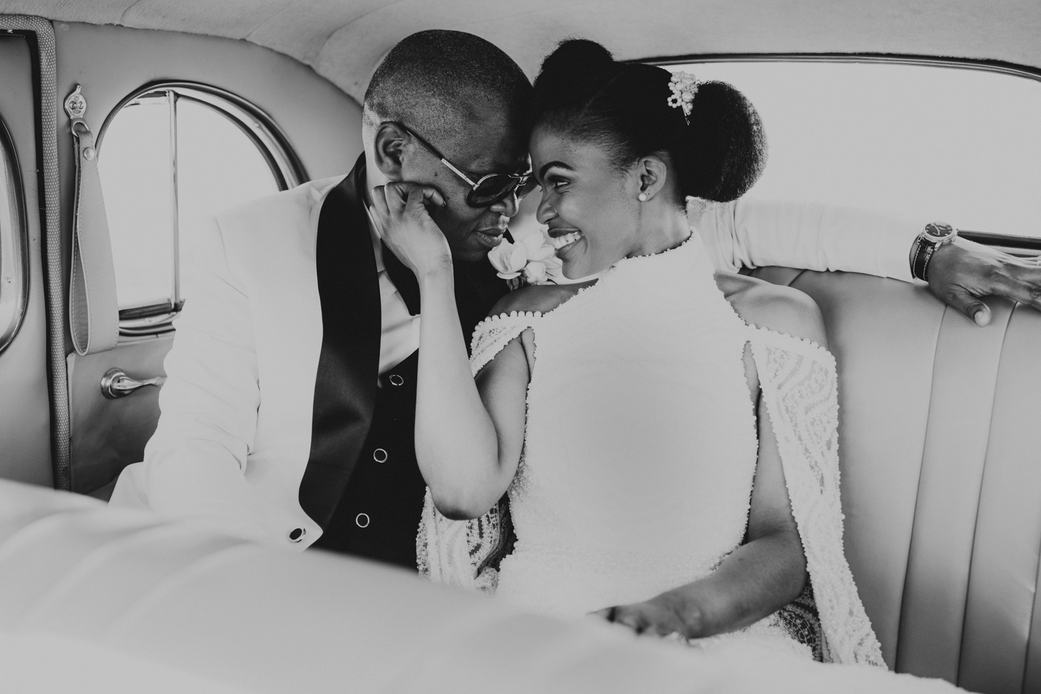 a black and white image taken by Vividblue of the bride and groom siting in the car and looking at each other at Val de Vie.