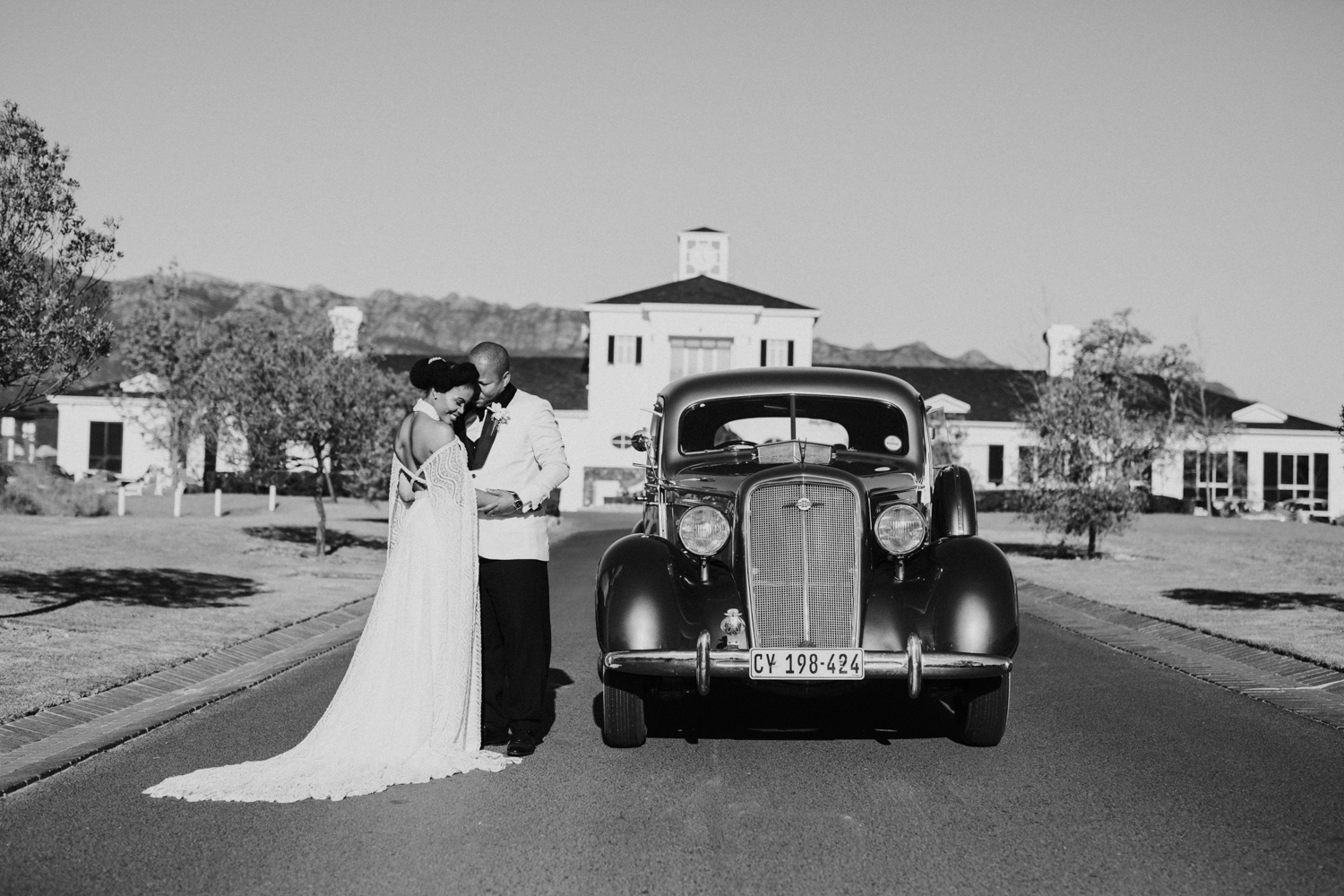 a black and white image of the bride and groom standing next to their wedding car at Val de Vie