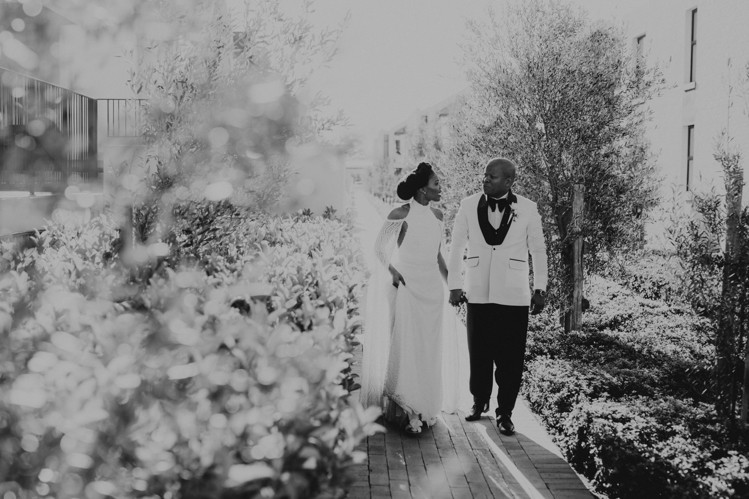 a black and white Image taken by Vividblue of the Bride and the groom walking and holding hands at Val De Vie.