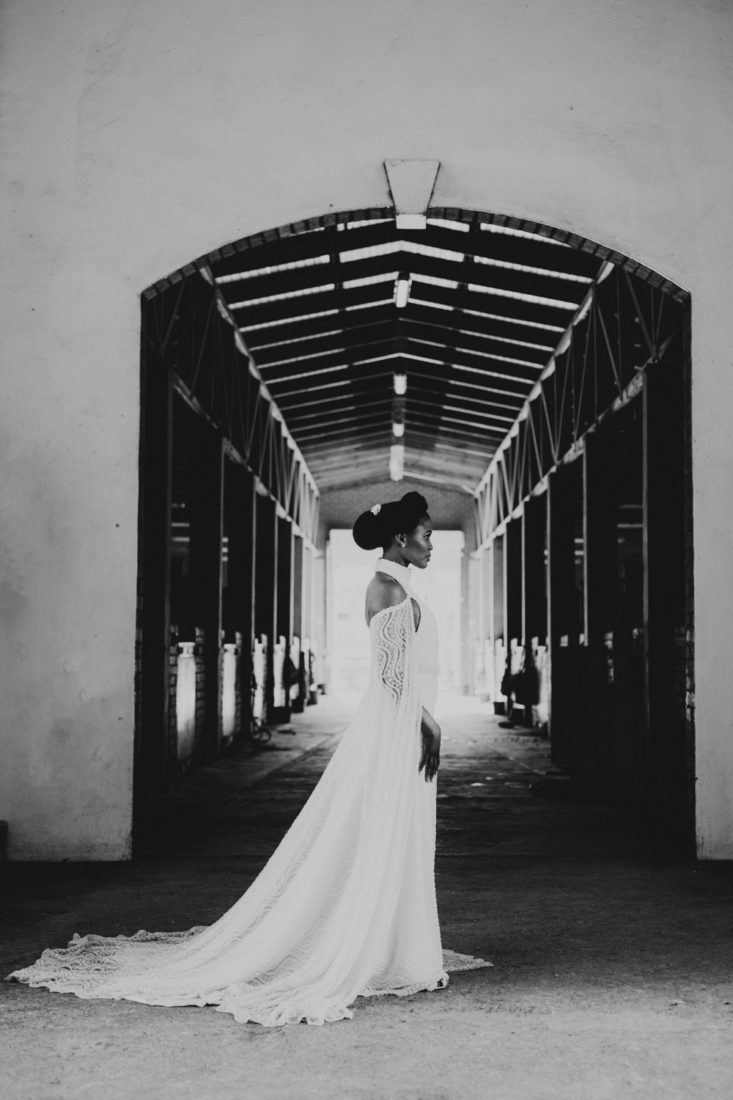 a black and white image taken by Vividblue of the bride in a lace wedding dress standing in a big doorway at the stables at Val De Vie.