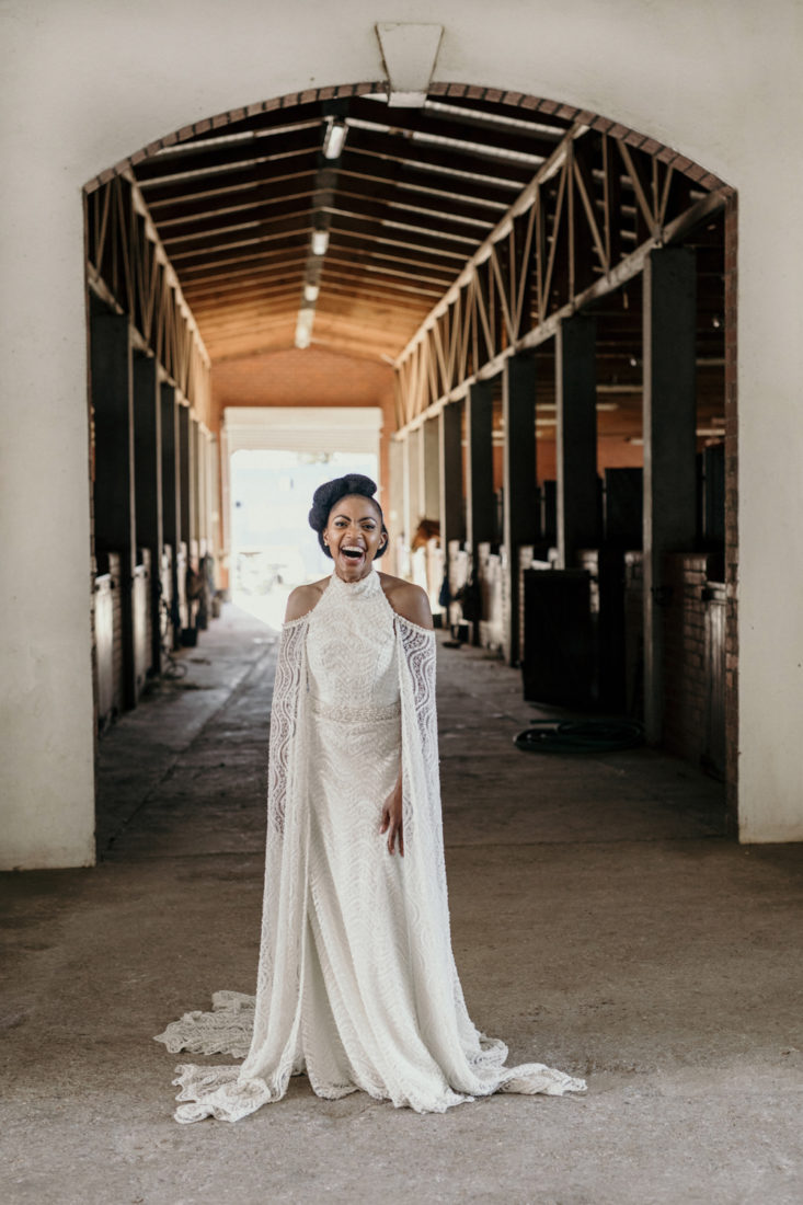 an image taken by Vividblue of the bride in a lace wedding dress standing and smiling in a big doorway of the stables at Val De Vie.