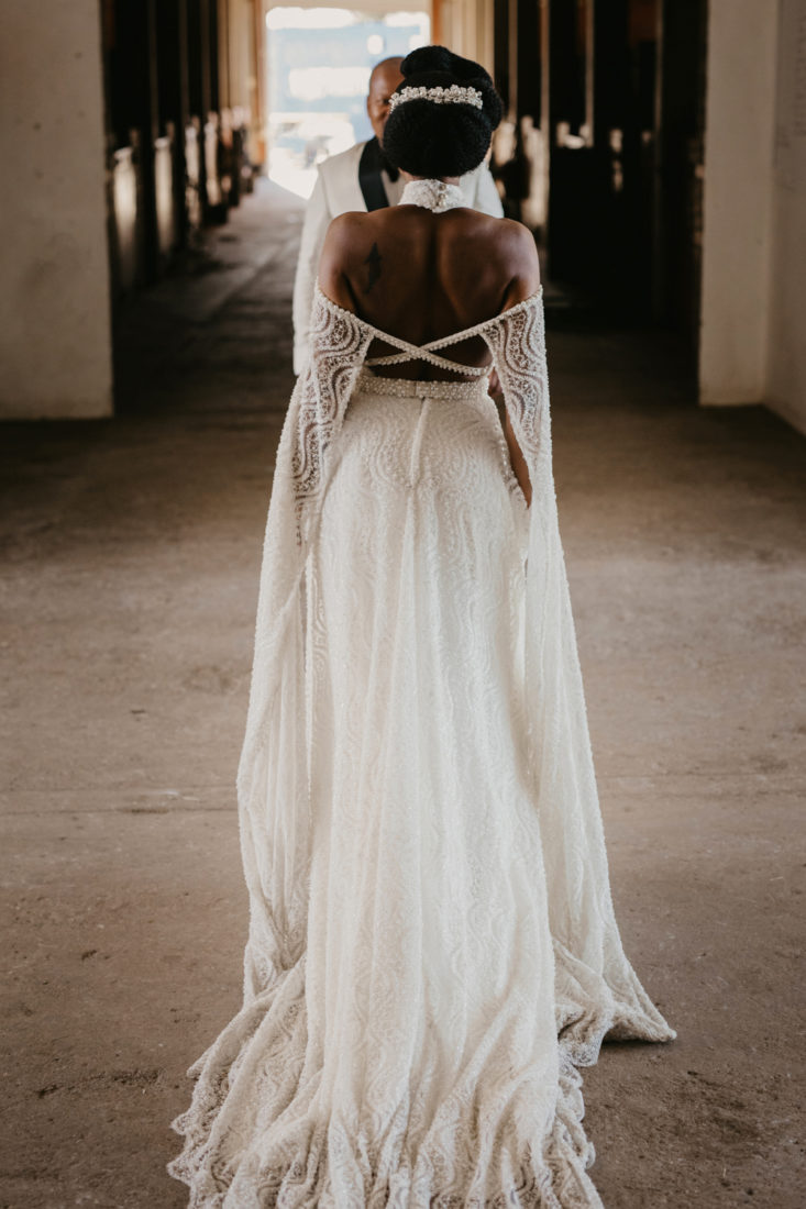 an image taken by Vividblue of the bride in a lace wedding dress standing towards the groom in a big doorway at the stables at Val De Vie.
