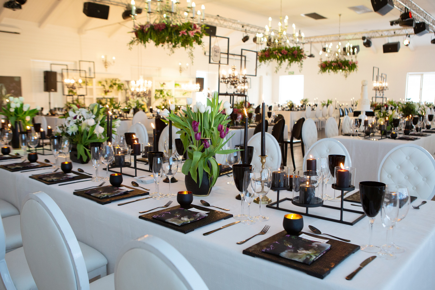 an image taken by Vividblue of the decor of a wedding at Val De Vie, black vases with purple and white floral arraignment white table cloths and black chairs