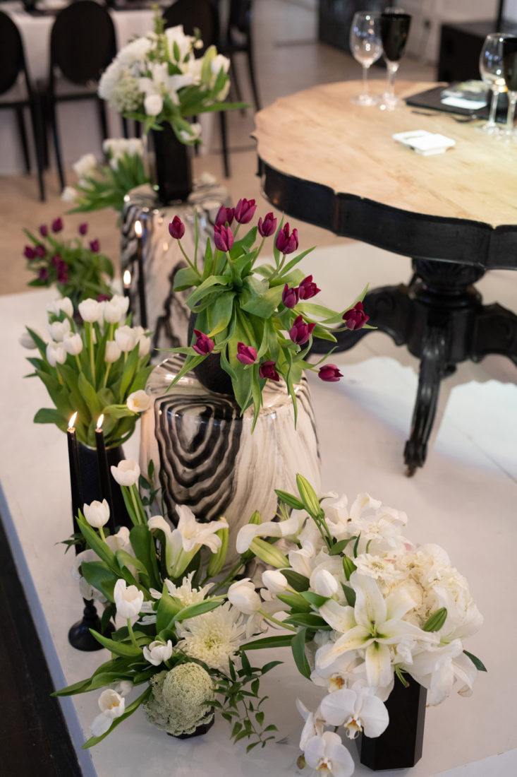 an image taken by Vividblue of the decor of a wedding at Val De Vie, black vases with purple and white floral arraignment