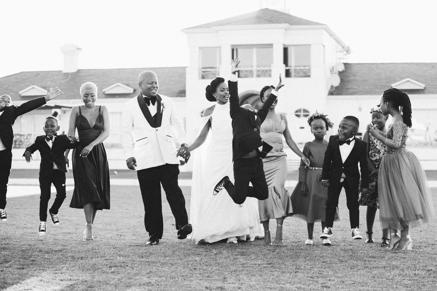 a black and white image taken by Vividblue of the bridal party and kids jumping in the air at a wedding in Val De Vie