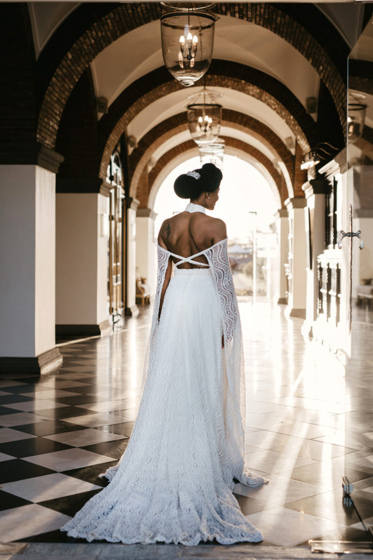 an image taken by Vividblue of the bride walking inside Val de Vie with her back facing the camera.