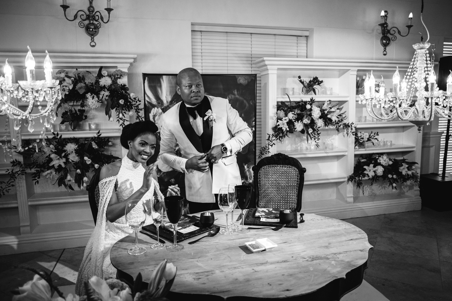 a black and white image taken by Vividblue of the bride and groom siting at their wedding table at Val de Vie.
