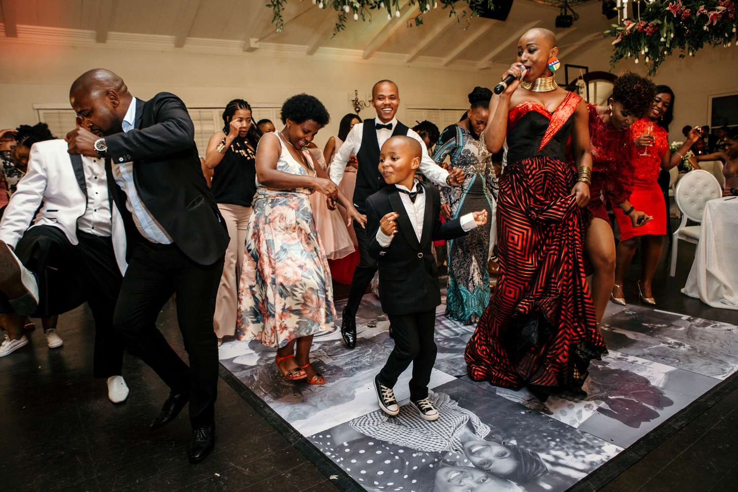 an image taken by Vividblue of a woman in a red and black dress singing and everyone dancing around her at the wedding at Val de Vie.