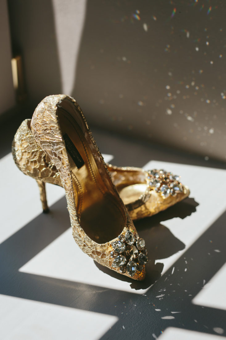 golden wedding shoes that sparkle because of the sunlight coming from the window.