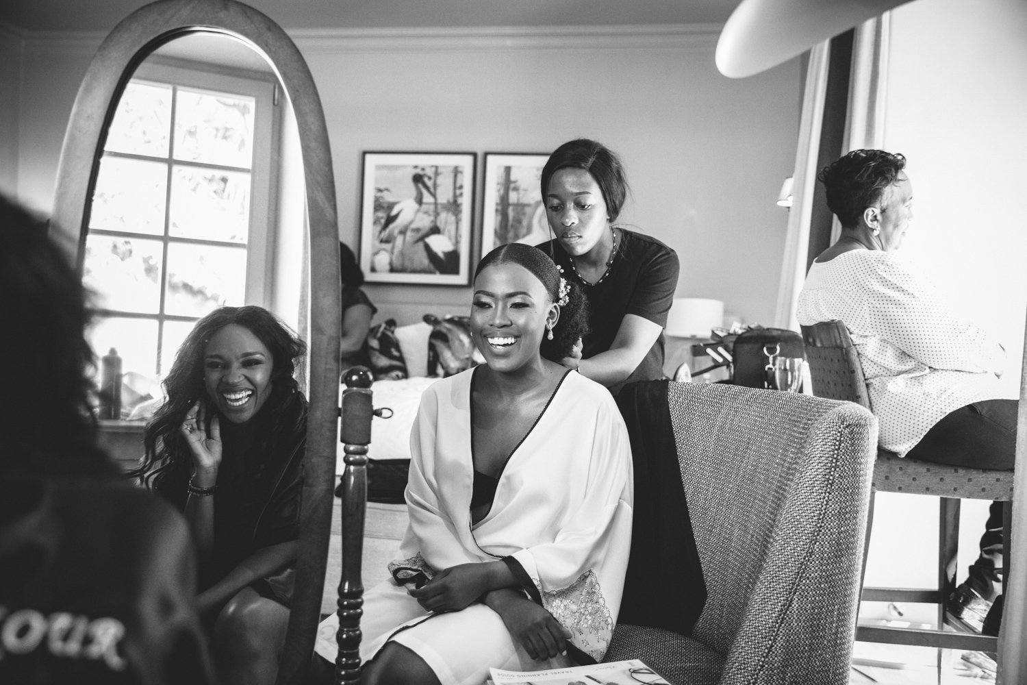 a bride getting ready for her wedding, laughing with her bridesmaid.