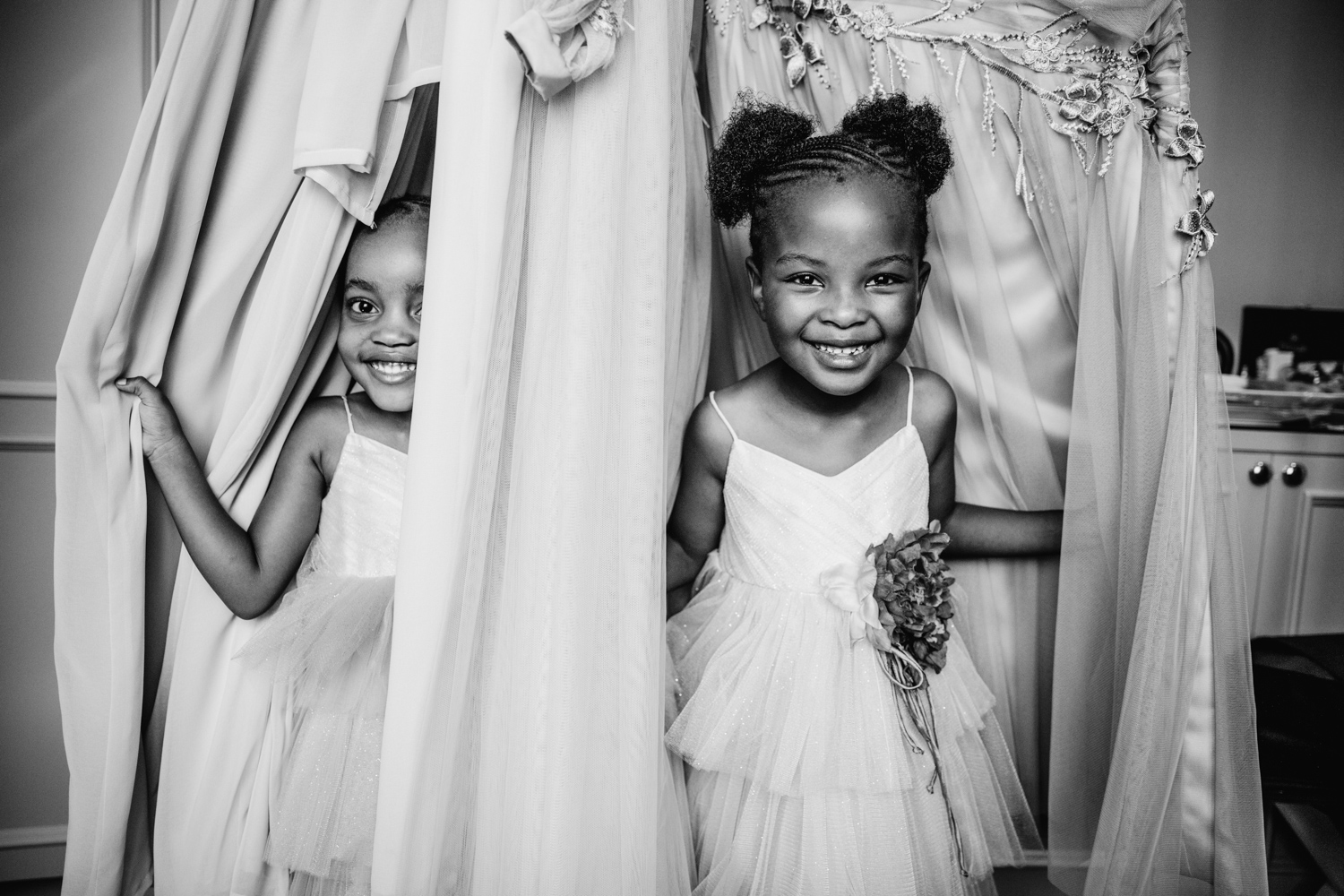 Two flower girls playing under the hanging bridesmaid dresses when everyone is getting ready for the wedding.