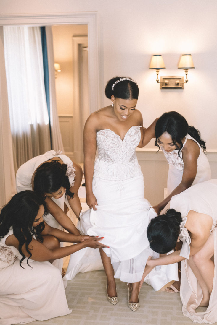 Four bridesmaids putting the brides golden shoes on for her wedding day.